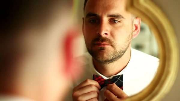 Man getting ready in front of a mirror adjusting his plaid textured bow tie Royalty-free stock video