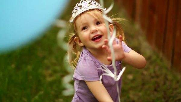 Little girl running through a back yard holding balloons and laughing Royalty-free stock video