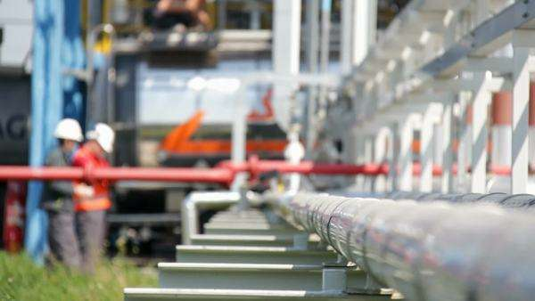 Pipes at an oil distribution centre, with technicians in the background. Royalty-free stock video