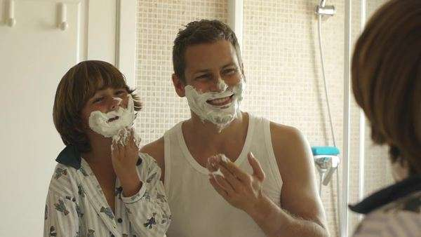 Father and son with shaving cream on their faces. Royalty-free stock video
