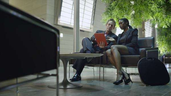 Two colleagues review information on an ipad while sitting in an atrium lobby Royalty-free stock video