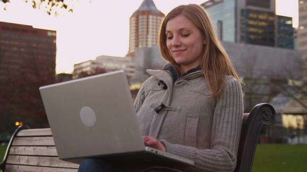 Young woman sits on park bench using laptop computer Royalty-free stock video