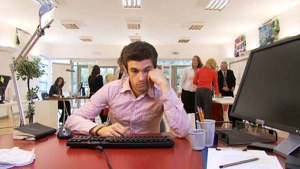 Bored male office worker struggles to stay awake at his desk Royalty-free stock video