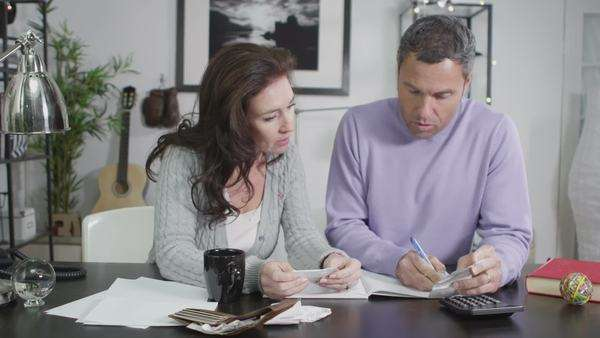 An attractive Caucasian couple sit down to work out their household accounts. In slow motion. Royalty-free stock video