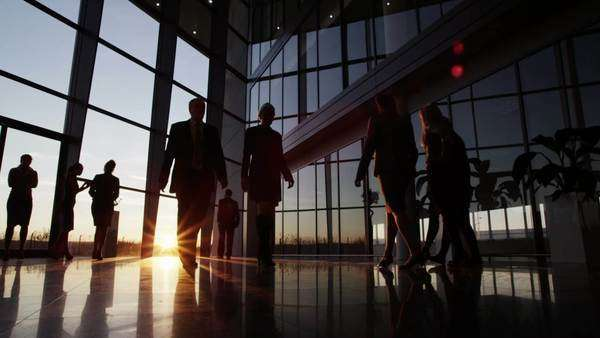 Silhouettes of a diverse group of business people walking through a modern glass fronted building at sunset. Royalty-free stock video
