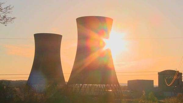 Timelapse shot of the sun setting behind a nuclear power plant. Royalty-free stock video