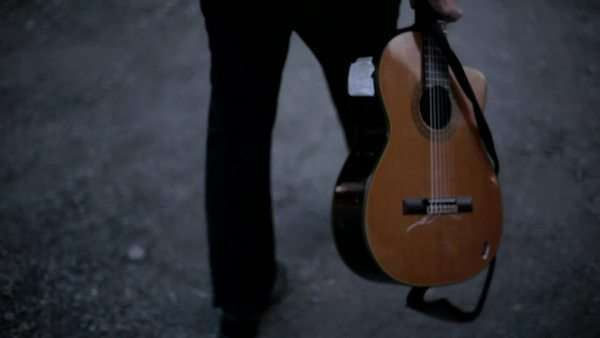 Musician carries his guitar as he walks down an alley Royalty-free stock video