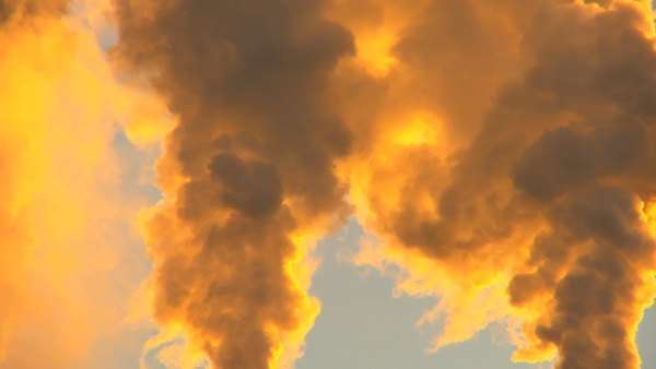 Smoke from power production plant seen golden at sunrise Royalty-free stock video