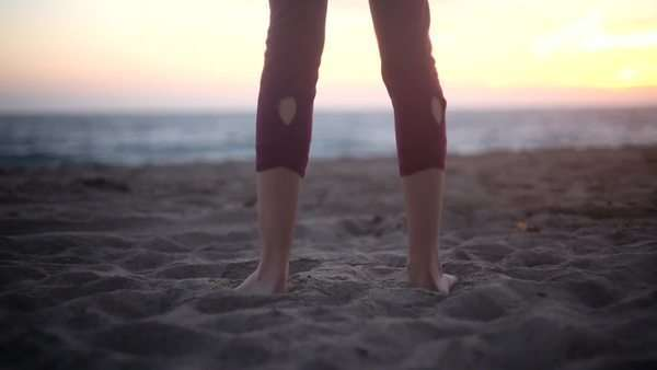 Women's legs doing a rotating jump on sandy beach Royalty-free stock video