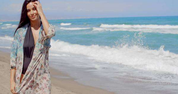 3dbcdfa241 Smiling pretty young woman wearing summer outfit walking at the beautiful  beach on a tropical climate.