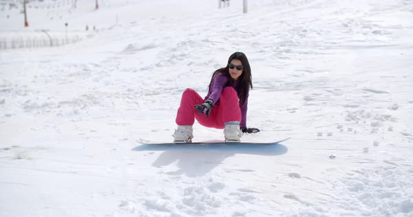174edfbb1b Cute woman with long hair and sunglasses laughing as she falls with her  snowboard on the snow on ski slope - Stock Video Footage - Dissolve