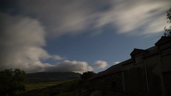 Moon-lit clouds roll over Mt Snowdon at night. There is a barn in the foreground which is illuminated at times by cars driving on the road below. Royalty-free stock video
