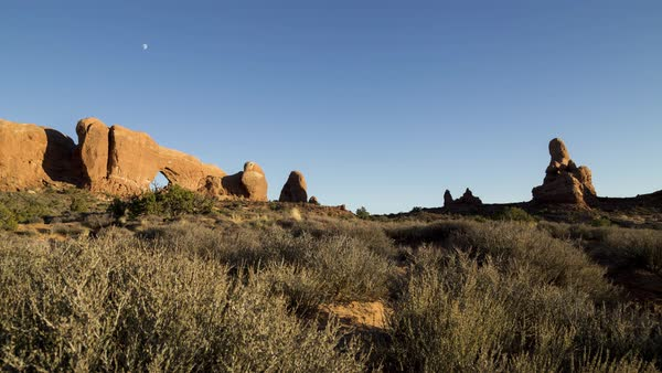 Sunset in Arches over an arch as the moon rises and people flock to see sunset from a higher vantage point. Royalty-free stock video