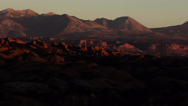 Sunset over hills and rocks in Arches, looking towards distant mountains. Royalty-free stock video