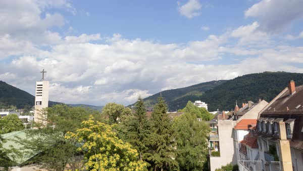 Looking out over Heidelberg from a roof terrace. Clouds fly over the Old Town and the castle in the distance. Royalty-free stock video