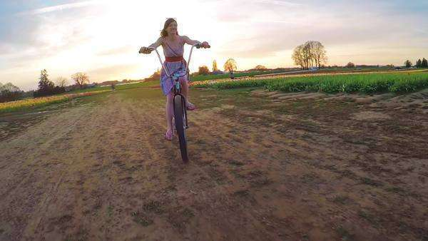 Low Angle View Of Happy Young Woman Riding A Vintage Bicycle In A Field Of Tulips During Sunset Stock Footage
