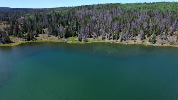 Aerial view of Lyman Lakeside, backing across the lake, with a boat in the  middle of the water in Utah  stock footage