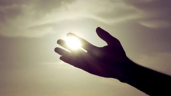Slow motion shot of a silhouetted male hand against a sun and sky background, grasping the sun and letting sunlight pass through the fingers. Royalty-free stock video
