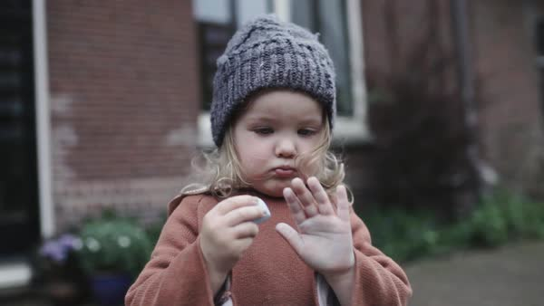 Medium shot of a little girl trying to draw to her hand with a chalk Royalty-free stock video