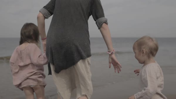 Hand-held shot of a mother running with her children on a beach Royalty-free stock video