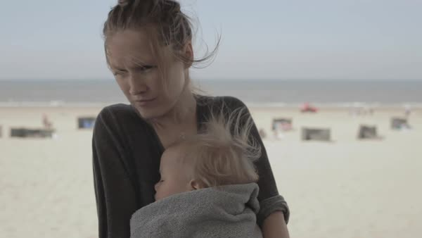 Hand-held shot of a woman holding her child in her arms on a beach Royalty-free stock video