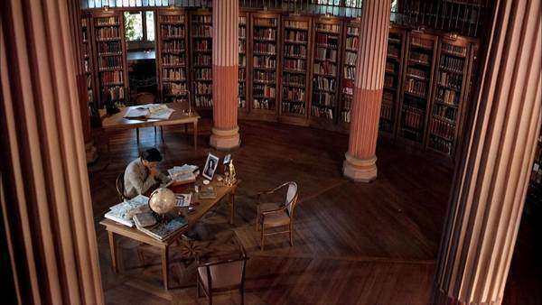 High-angle shot of a student studying in grand library. Originally sourced from 70mm film Rights-managed stock video