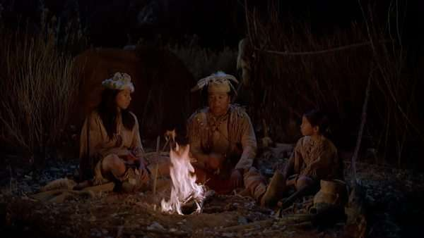 Hand-held shot of a Native American family telling stories around campfire. Originally sourced from 70mm film Rights-managed stock video