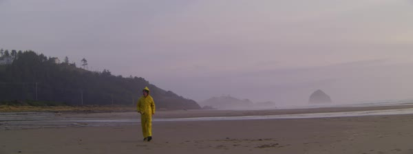 Slow motion shot of a man walking alone on the beach on a rainy day Royalty-free stock video