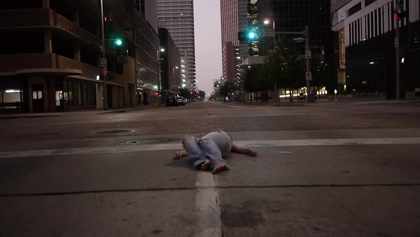Medium shot of a person lying on an empty road Royalty-free stock video
