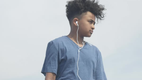 Dolly shot view of a young boy listening to music with headphones Royalty-free stock video