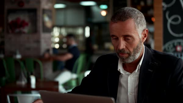 Businessman using laptop and drinking coffee at cafe. Royalty-free stock video