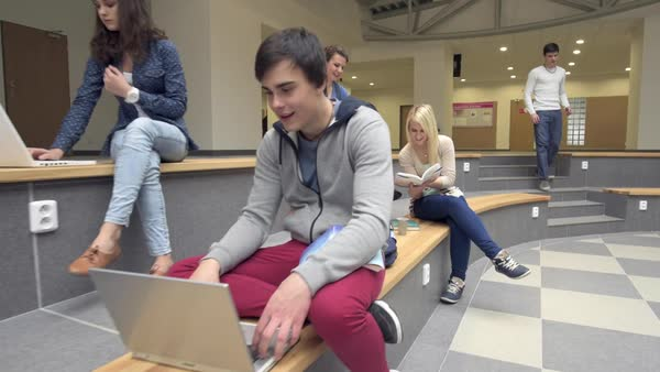 Students sitting and learning with laptop on bench inside modern university hall tracking shot slow motion Royalty-free stock video