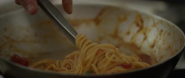 Tilt-up shot of a chef taking pasta out from a pan with kitchen tweezers Royalty-free stock video
