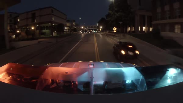Point of view from the top of an emergency ambulance racing down the street to an urban hospital at night with flashing lights at the bottom of frame. Royalty-free stock video