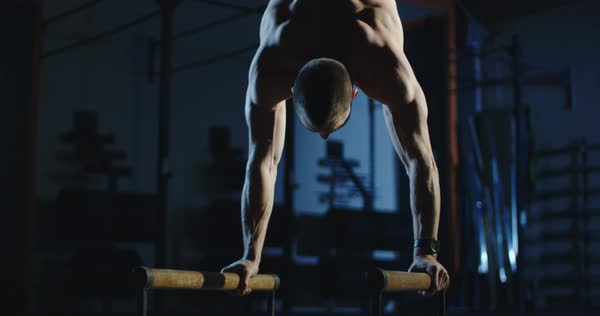 Muscular shirtless man working out on bars training gymnastics in dark gym   stock footage