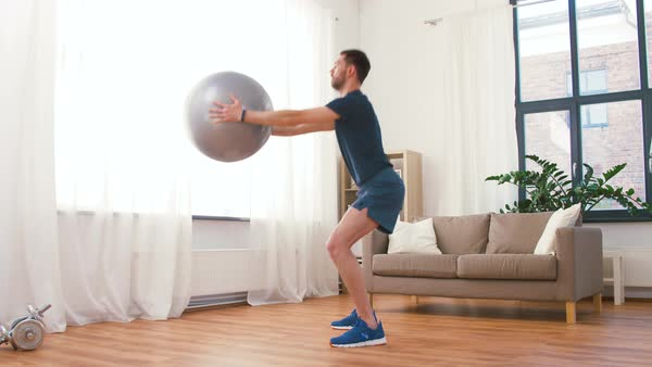 Man exercising and doing squats with ball at home stock footage