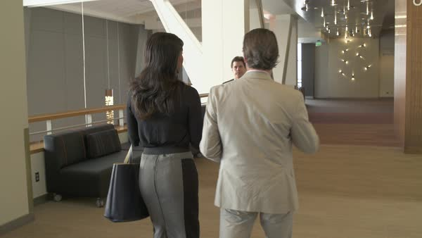 Tracking shot of a man and a woman walking in a conference center Royalty-free stock video