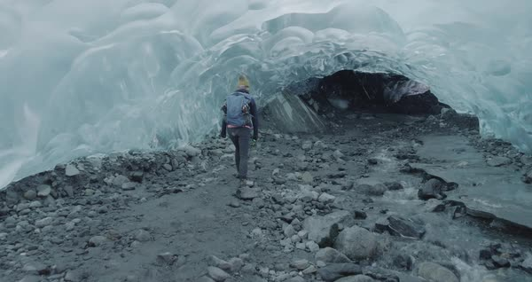 Drone shot of a woman walking in the Mendenhall Ice Caves Royalty-free stock video
