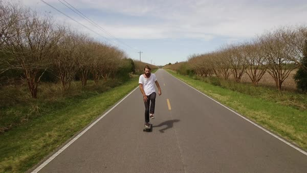 Drone shot of a man skateboarding on a rural road Royalty-free stock video