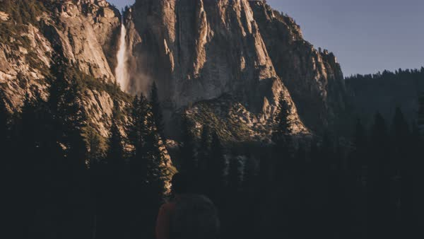 A hiker walks below Yosemite falls Royalty-free stock video