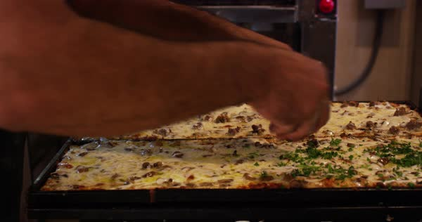 Pizza chef sprinkling oregano on pan of pizza Royalty-free stock video