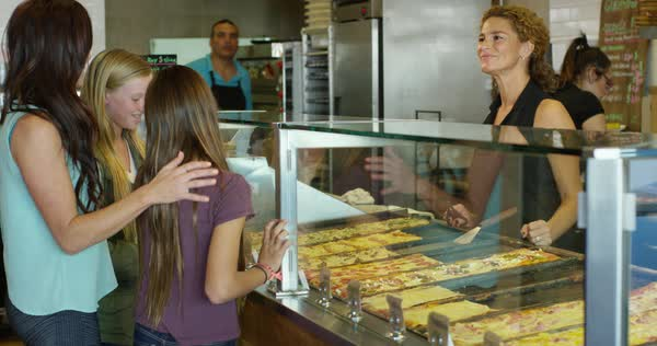 Waitress explaining pizza choices to mother and daughters Royalty-free stock video