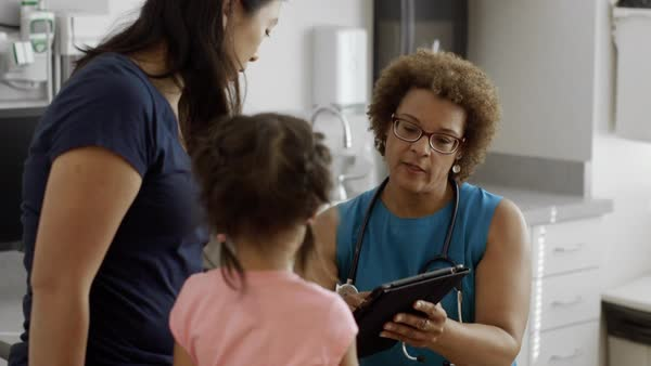 Pediatrician with digital tablet talking to mother and daughter Royalty-free stock video