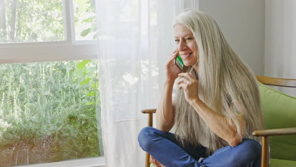 a3b4dabb8a68 Mature Caucasian woman sitting in livingroom talking on cell phone ...