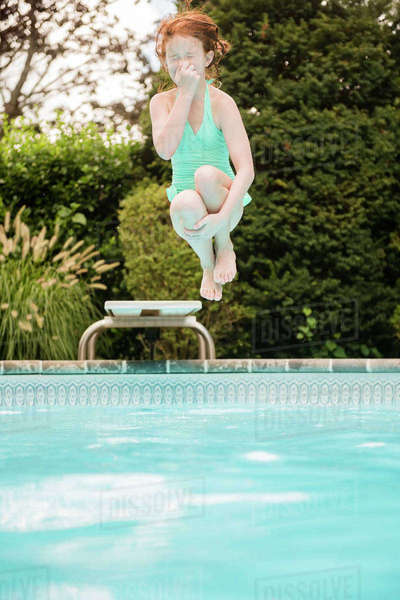 Caucasian Girl Holding Nose Jumping Off Diving Board Into Swimming Pool Stock Photo Dissolve