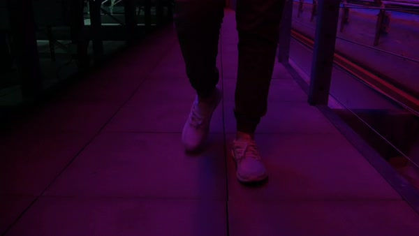 Hand-held shot of legs of a man walking on a rooftop lit by a neon sign Royalty-free stock video
