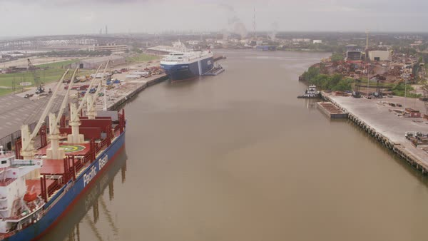 Cargo ships moored at Houston Ship Channel, Refinery in background,  Houston, Texas, United States of America  Shot in 2017  stock footage