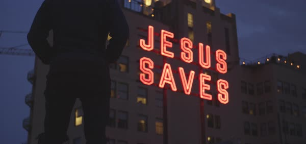 Hand-held shot of a man looking at Jesus Saves neon sign on a hotel Royalty-free stock video