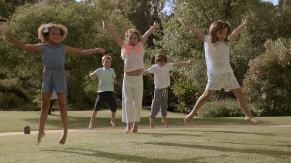 Five children doing star jumps in park Royalty-free stock video