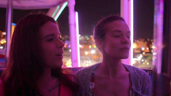 Two friends on a ferris wheel at night Royalty-free stock video